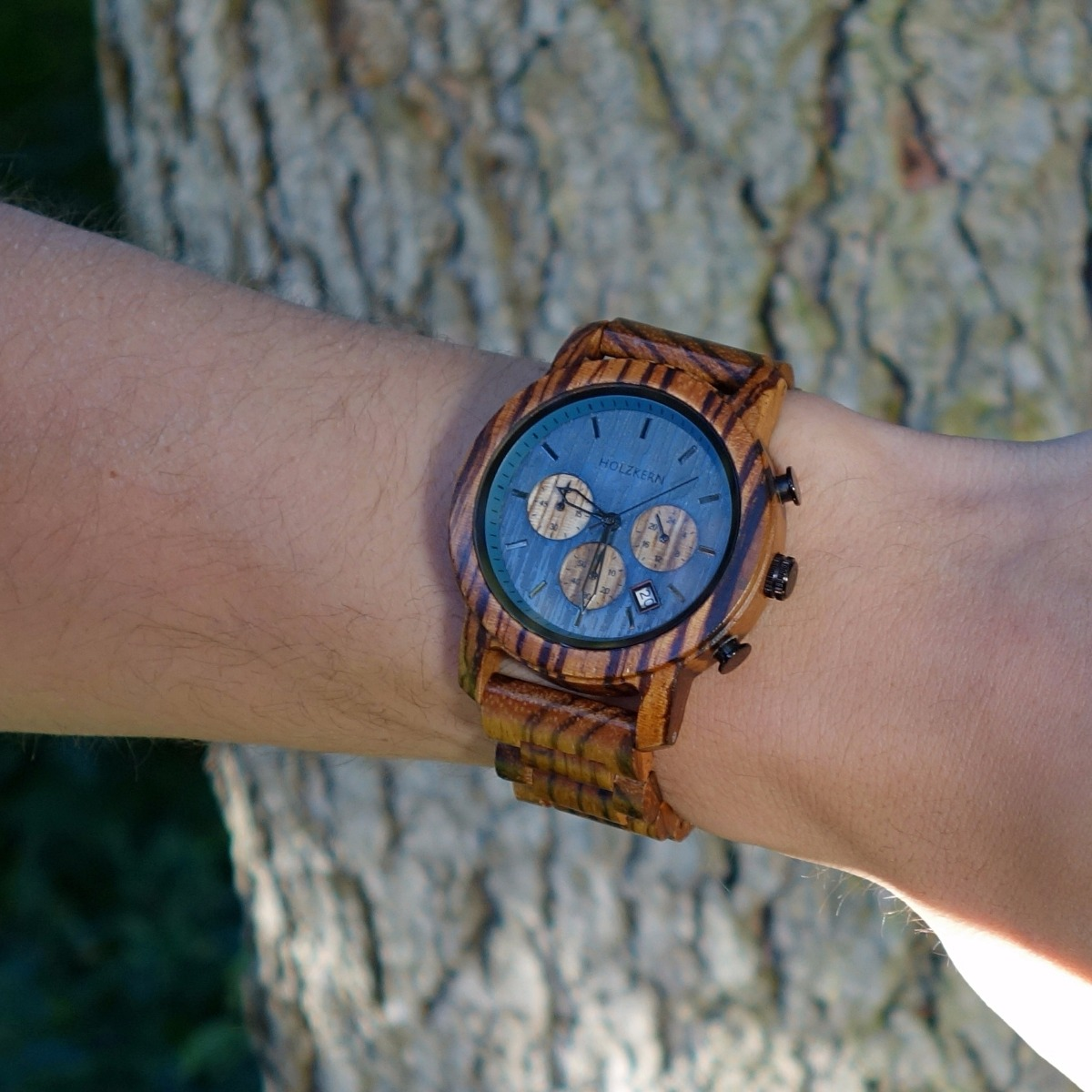 The wood watch Mountainlake, a chronograph made of zebrawood on the wrist of a man
