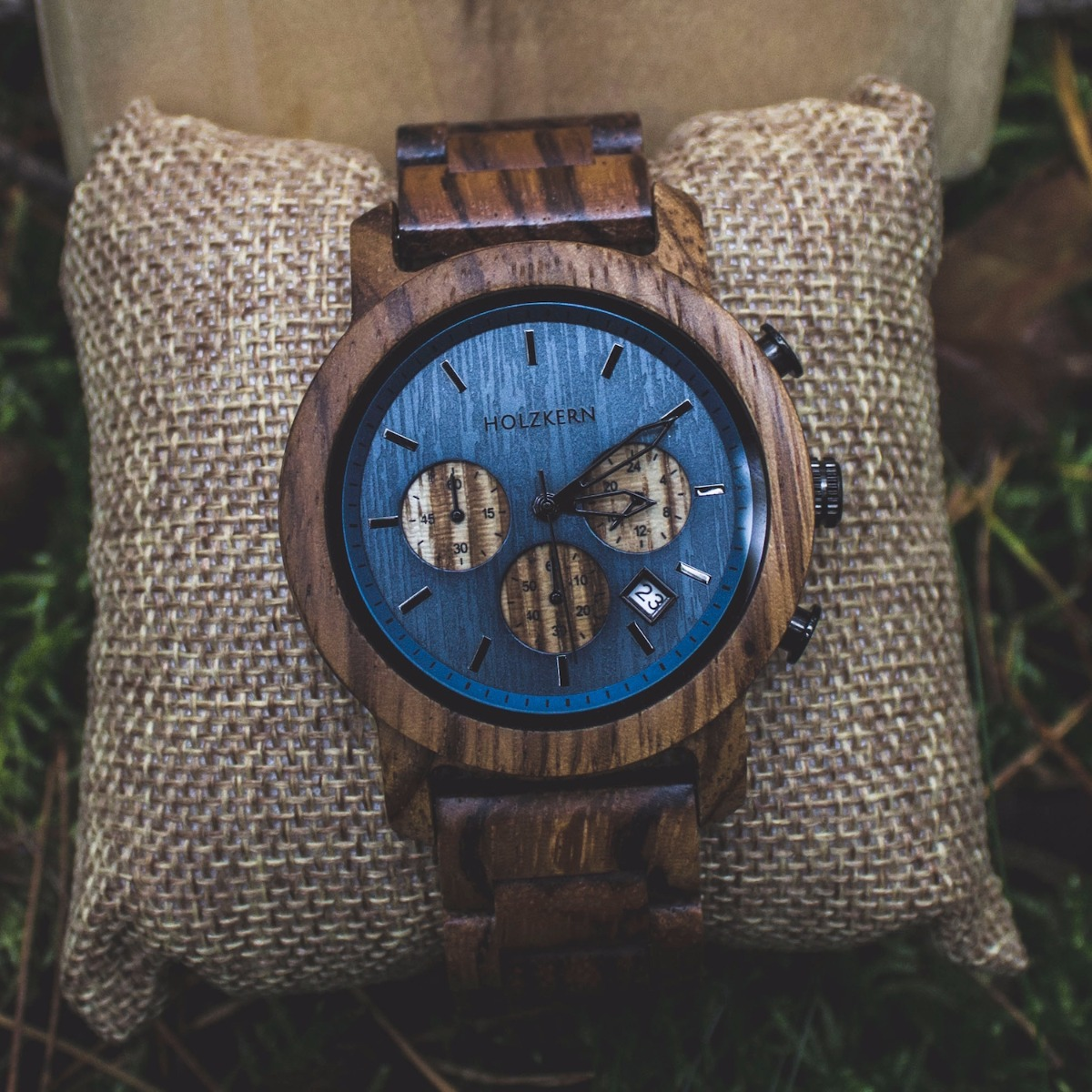 Wooden watch named Mountainlake made by Holzkern on a jewellery cushion