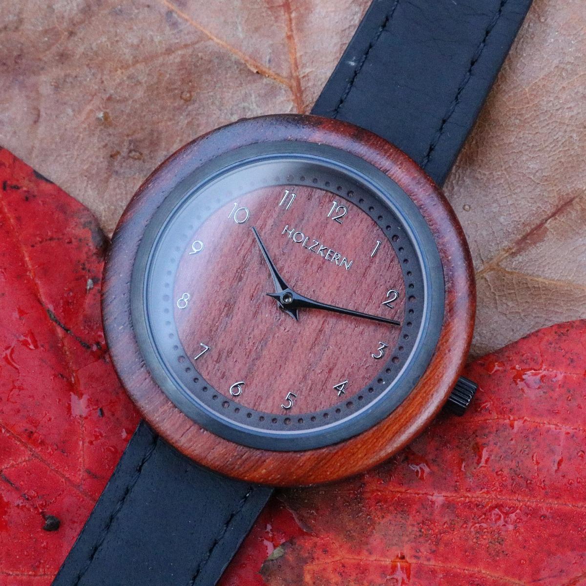 Die Holzkern Holzuhr Cape liegt auf bunten Herbstblättern