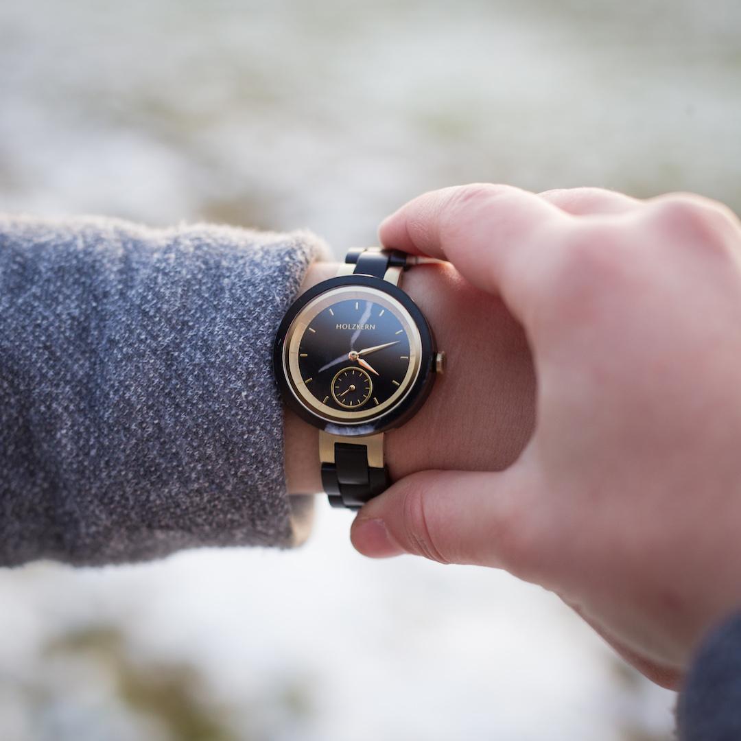 Ein Blick auf die Uhr zeigt die Holzkern Holzuhr Causeway am Damenhandgelenk, die schwarz mit gold auf eine besondere Art kombiniert