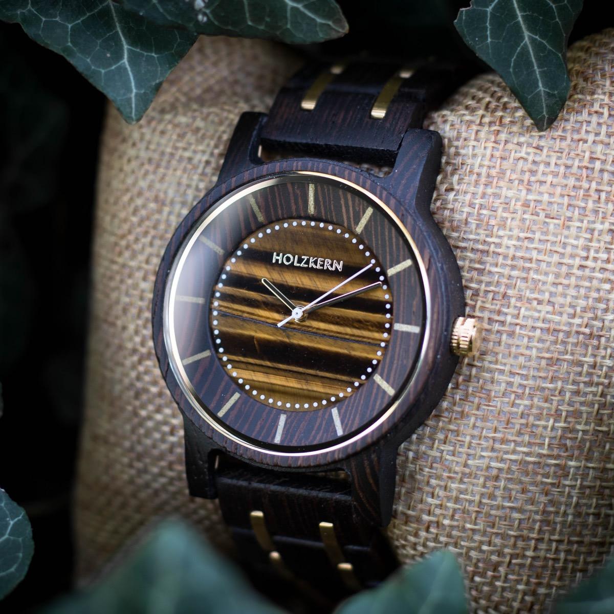 Eine Holzuhr von Holzkern namens Christoph mit einem einzigartigen Ziffernblatt aus echtem Tigerauge auf einem Uhrenpolster umgeben von Efeu
