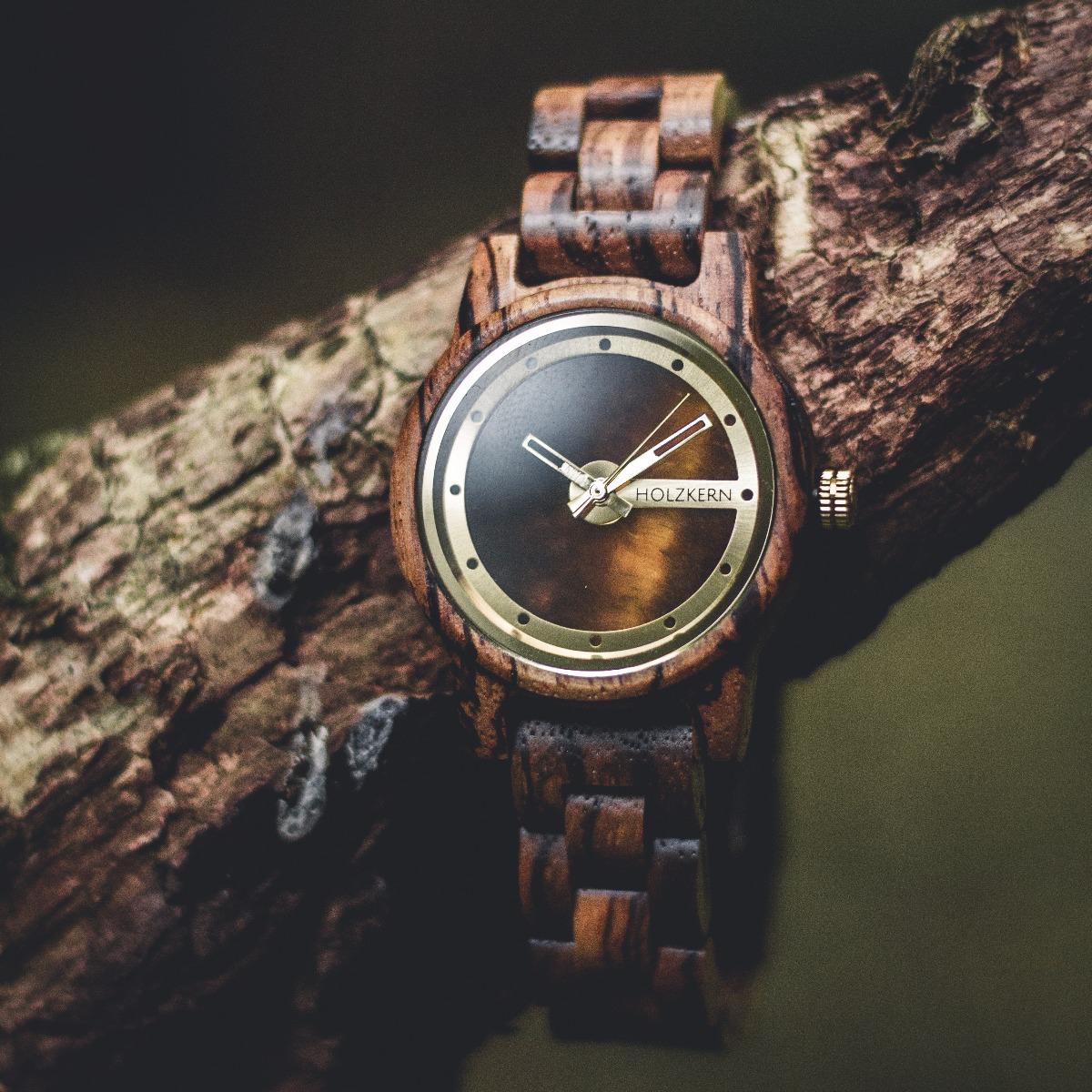 Die Holzuhr El Capitan von Holzkern hängt an einem Ast und schillert im Sonnenlicht durch das Ziffernblatt aus echtem Tigerauge