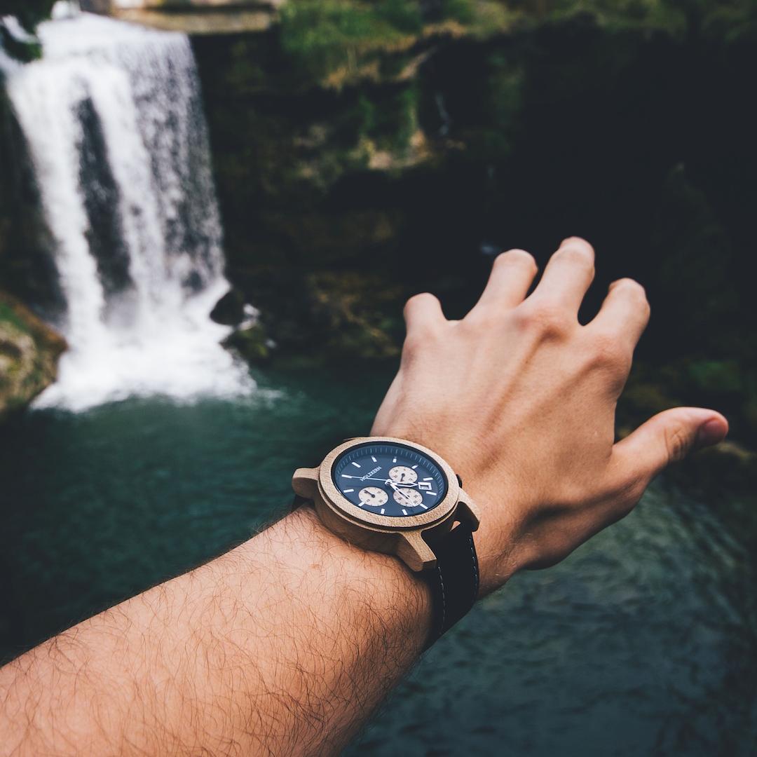 Man sieht die Holzuhr Lichtung von Holzkern am Handgelenk eines Herren, der in Richtung eines tosenden Wasserfalls greift