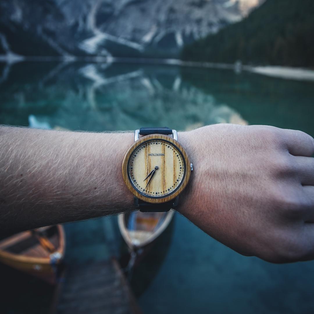 Holzuhr Merkur von Holzkern am Herrenhandgelenk vor einem See