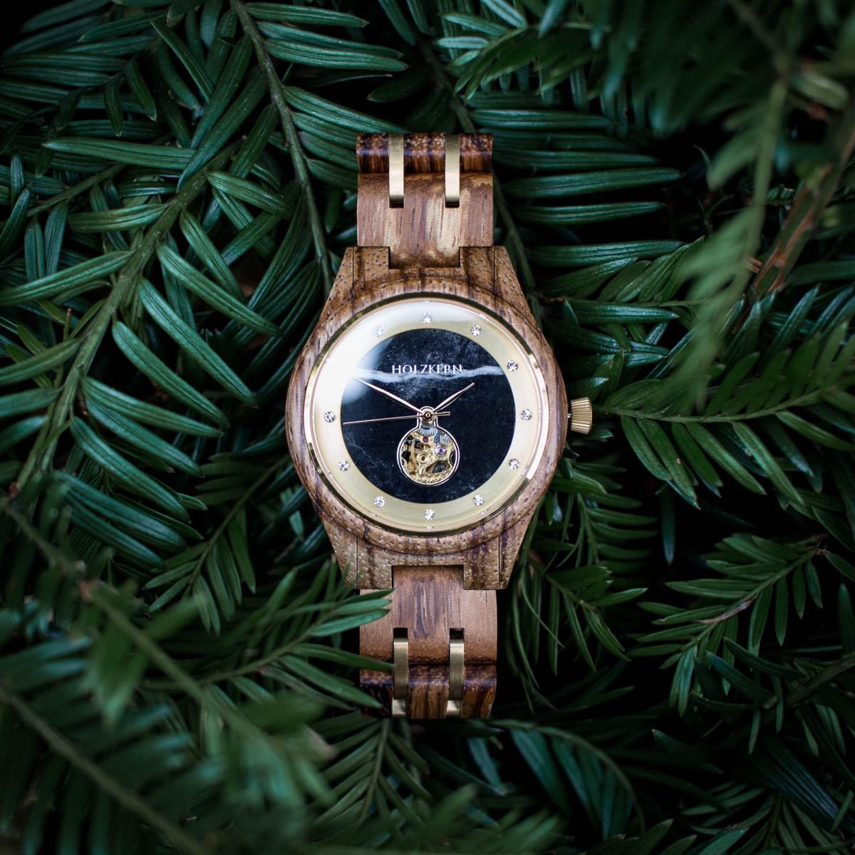 Holzkern Holzuhr Rapunzel für Damen mit Ziffernblatt aus schwarzem Marmor, Zebranoholz und Automatik-Uhrwerk liegt auf Tannenzweigen