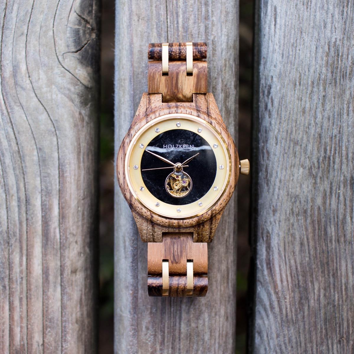 Automatik Holzuhr der Marke Holzkern mit Ziffernblatt aus schwarzem Marmor und Gehäuse aus Zebrano namens Rapunzel auf Holzbrettern