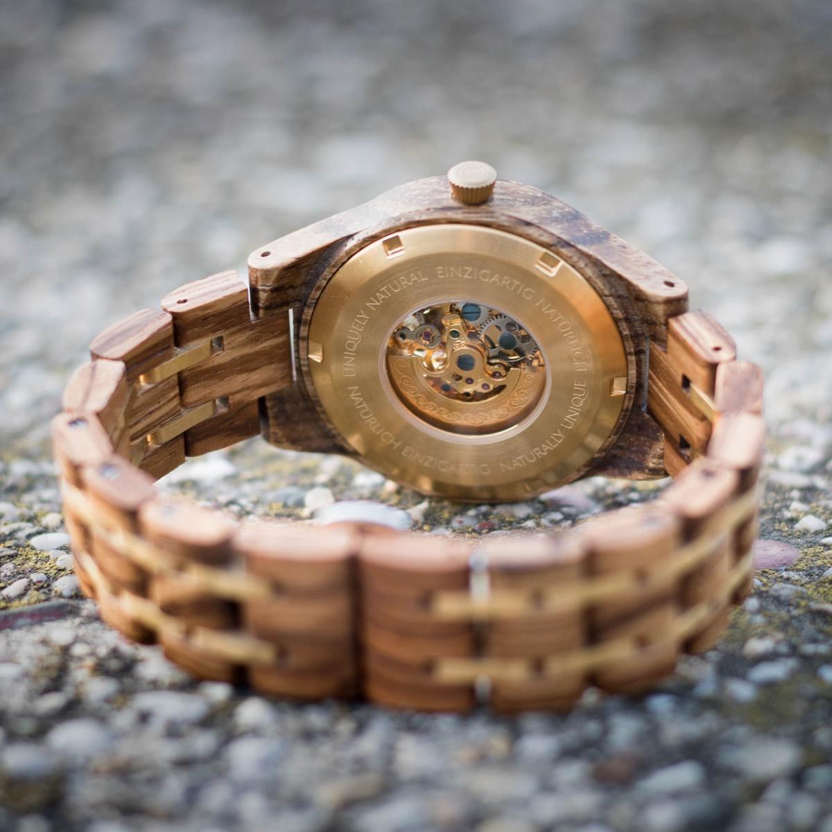 Unterseite der Damen-Holzuhr Rapunzel von Holzkern mit sichtbarem, mechanischem Uhrwerk und Zebranoholz und Felsuntergrund