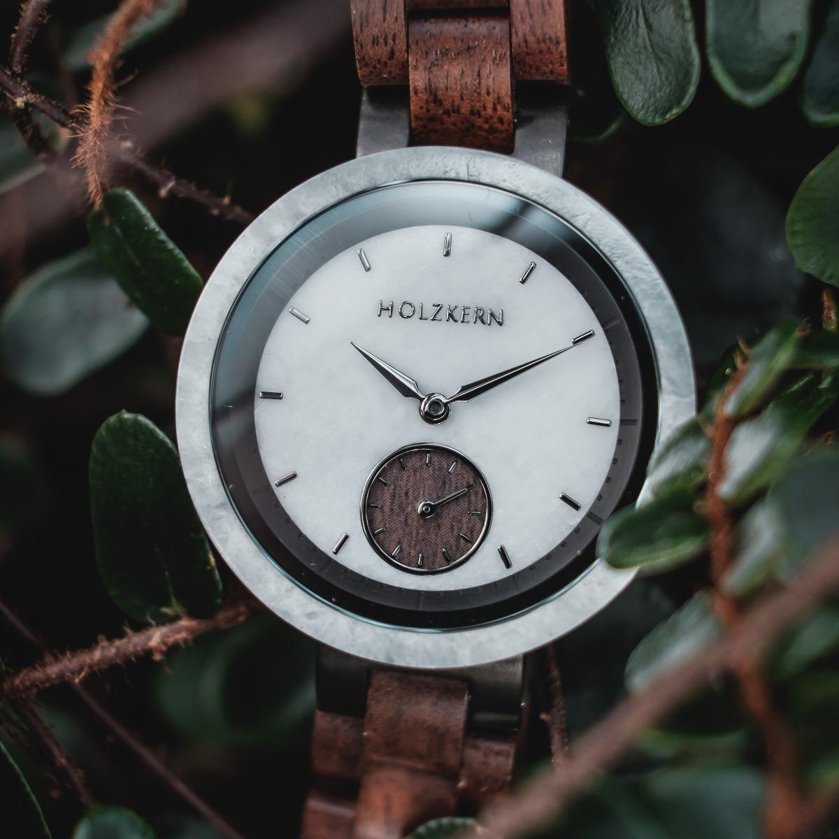 Nahansicht auf das weiße Marmorziffernblatt der Holzkern Damen Armbanduhr Steinen mit Blättern im Hintergrund