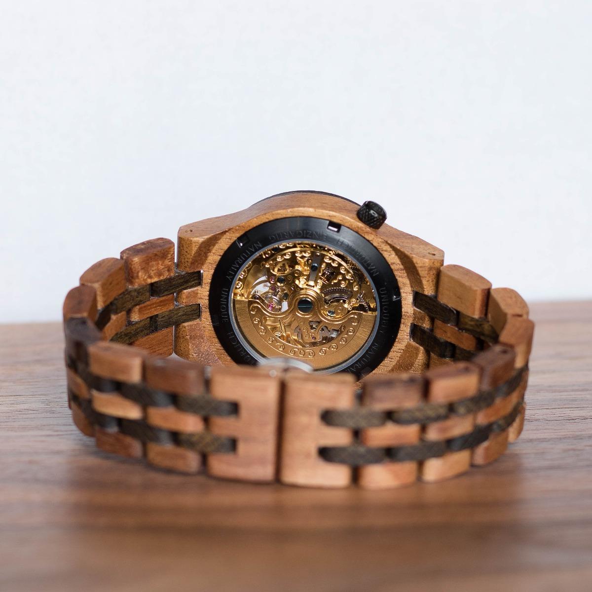 Hinteransicht auf das goldene mechanische Uhrwerk der Holzuhr Thales von Holzkern