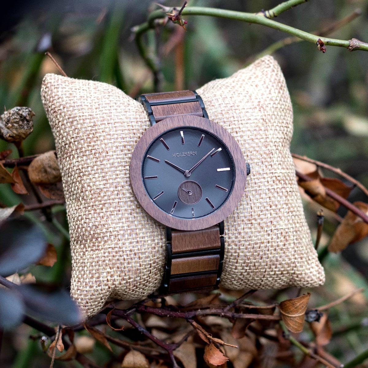 Holzuhr Tundra der Marke Holzkern aus Walnuss mit gemustertem schwarzen Edelstahl als Ziffernblatt auf einem Uhrenpolster umgeben von Geäst
