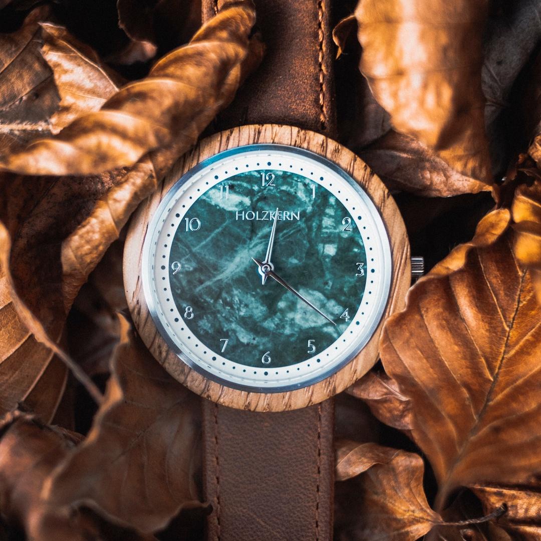 Die Herren Holzuhr Vertigo mit einem Ziffernblatt aus grünem Marmor im trockenen Herbstlaub
