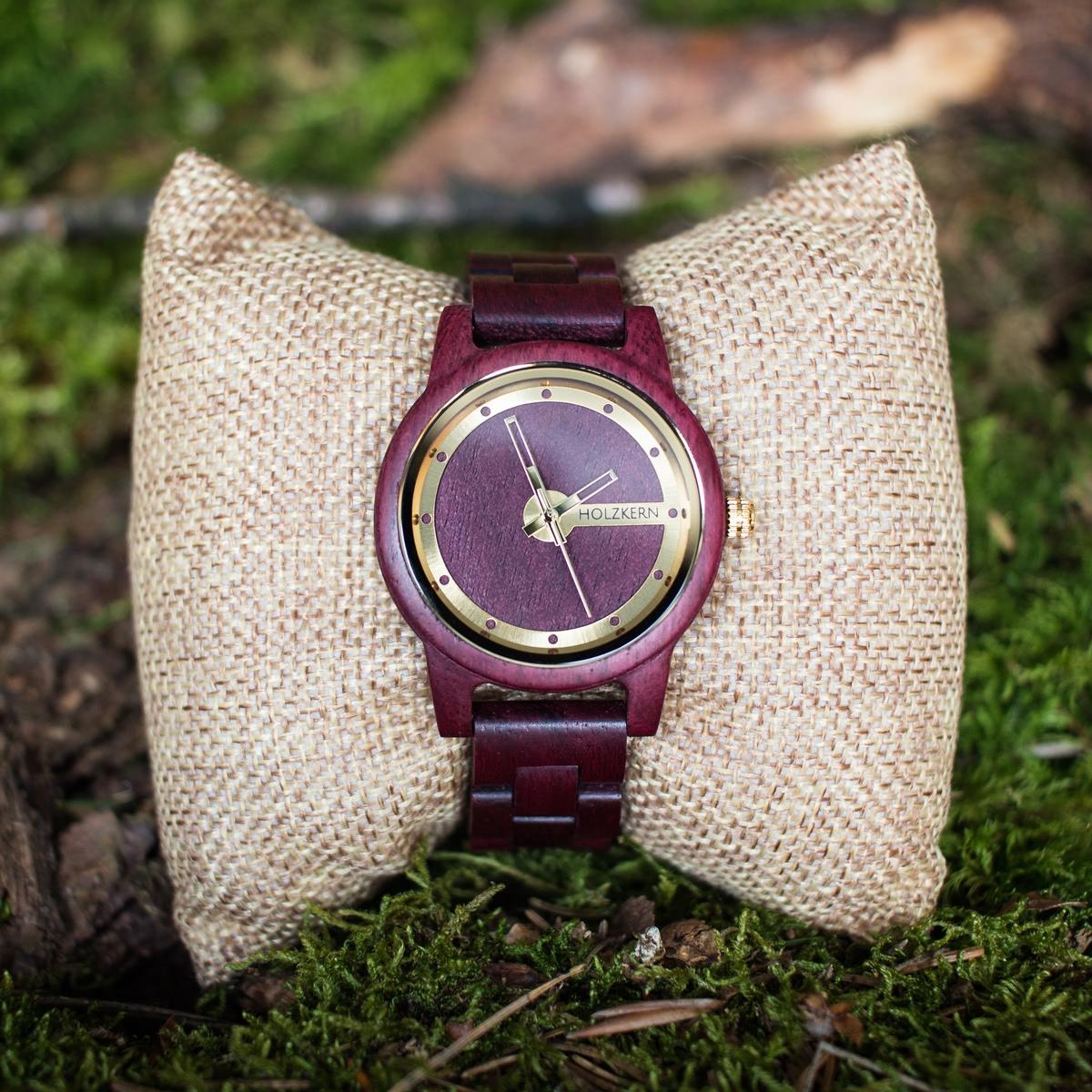 Damen Holzuhr der Marke Holzkern aus Amaranth auf einem Uhrenpolster im Wald
