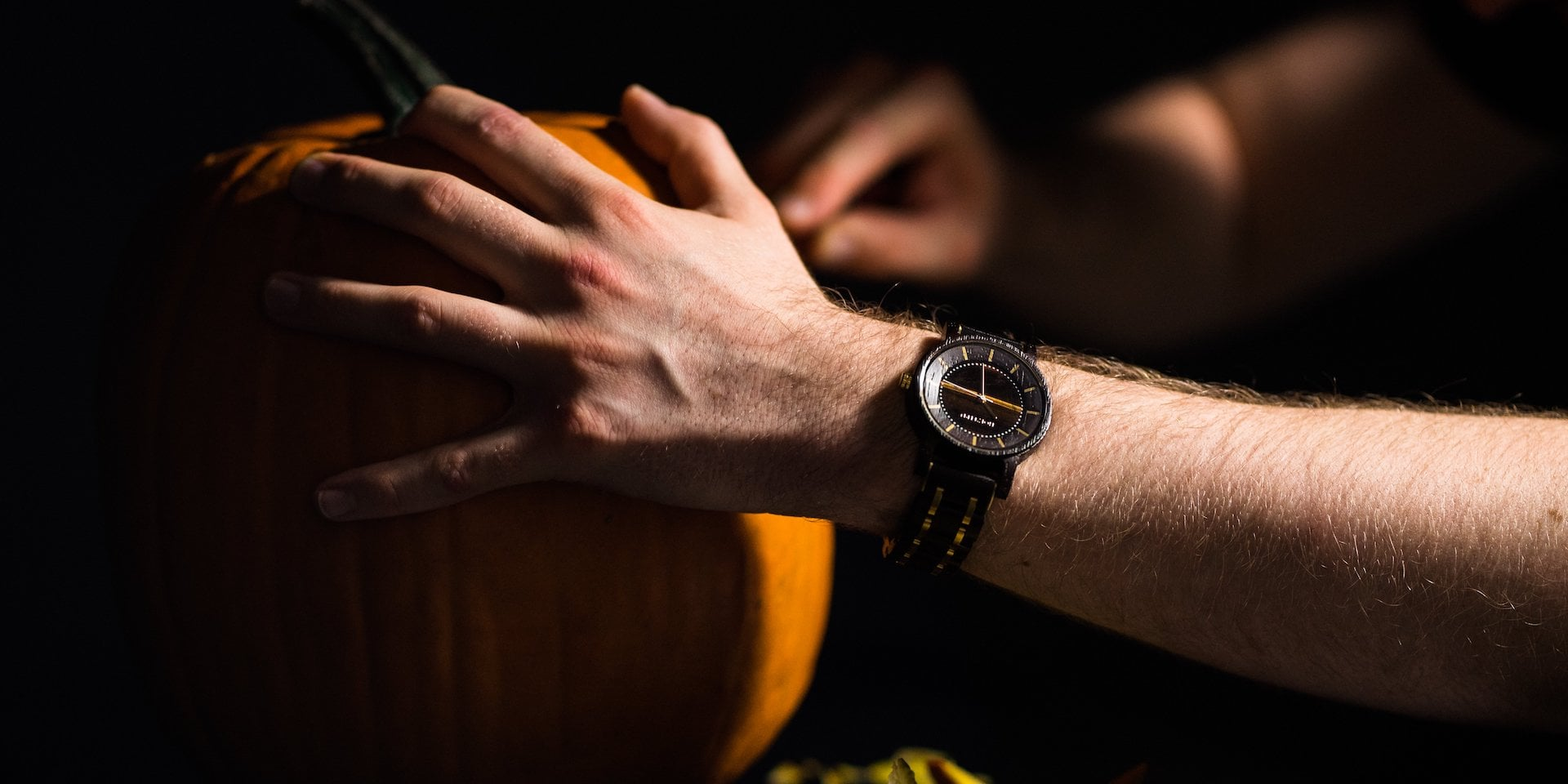 Unser Kollege Jannick trägt die Uhr Christoph beim Kürbisschnitzen